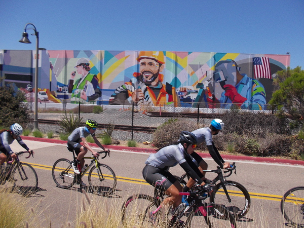 Cyclists following the Bayshore Bikeway head north on Marina Way past a mural on a building at the National City Marine Terminal.
