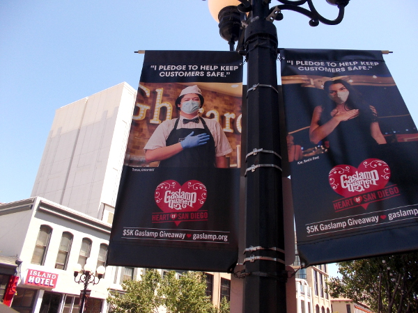 Gaslamp Quarter banners show workers at eateries pledging to keep customers safe during the coronavirus pandemic.