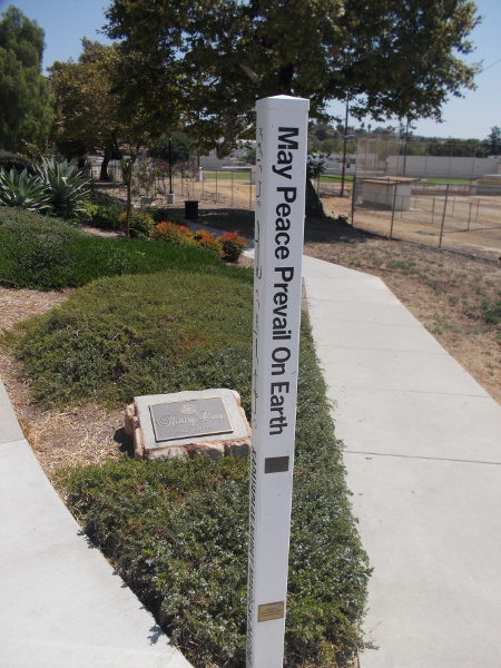 A pole at south end of Rotary Lane in Vista expresses May Peace Prevail on Earth in many languages. By the World Peace Prayer Society, 2018.