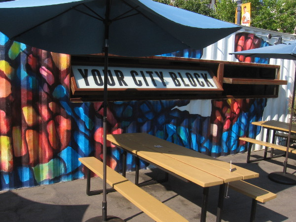 Colorfully painted shipping container by picnic benches indicates Quartyard is Your City Block.