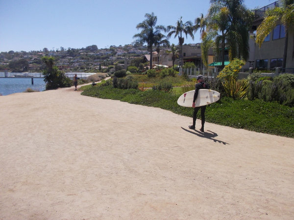 A surfer begins southwest down Point Loma's Bessemer Path beside San Diego Bay.
