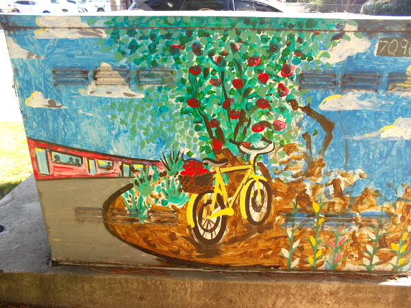 Bicycle by a fruit tree, and a trolley in the background.