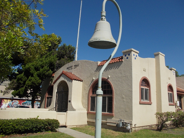 An iconic El Camino Real Bell stands near the historic San Ysidro Library on San Ysidro Boulevard.