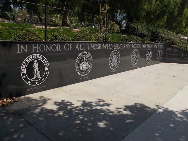 Branches of the United States Armed Services on a black marble memorial wall. In honor of all those who serve and protect . . . past, present and future.