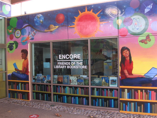 The mural on the other side of the entrance, with a window to the library bookstore. Students pursue scientific knowledge.