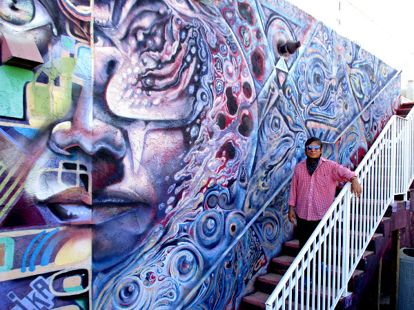 Francisco Morales, Gallery Director of The FRONT, smiles for a photo by this very cool mural.