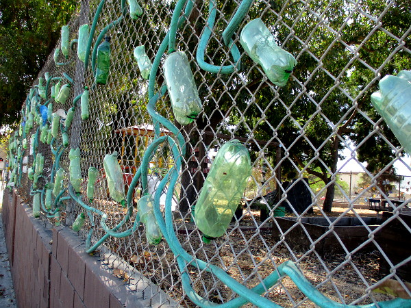 Recycled materials turned to art on the chain link fence.