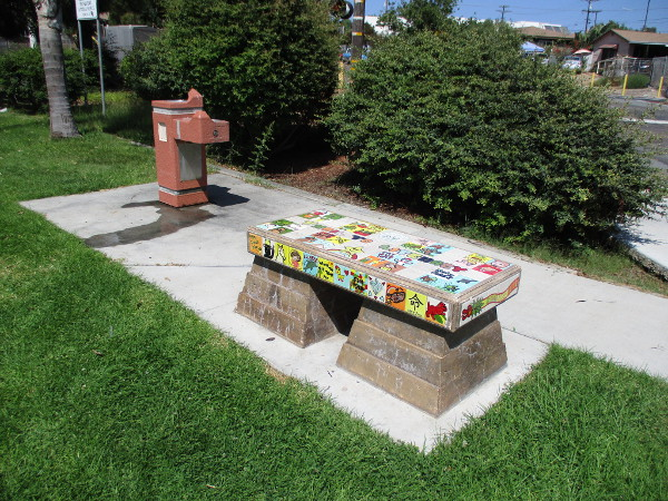 Trail to Literacy painted tile bench near a water fountain.