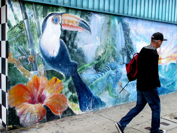 Somebody walks past a very colorful public mural in downtown Cardiff-by-the-Sea.