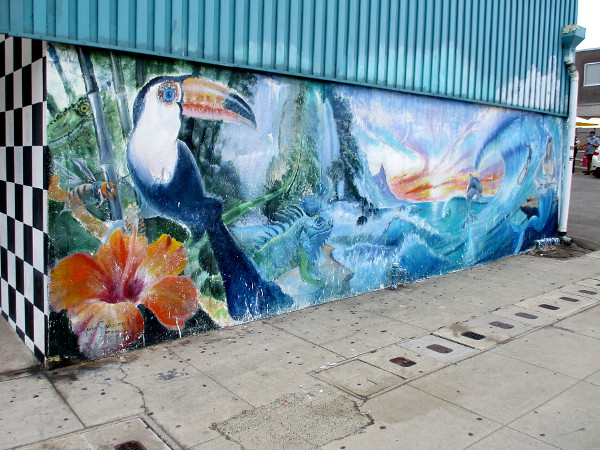 A tropical beach scene by Kevin Anderson Art Murals painted at the end of a strip mall building beside Aberdeen Drive.