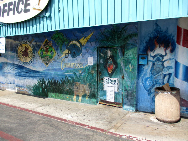 More painted scenes on an adjacent mural, in front of The Cardiff Office dive bar.