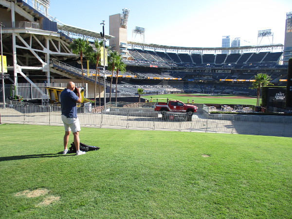 A photographer captures images of the Padres during batting practice.