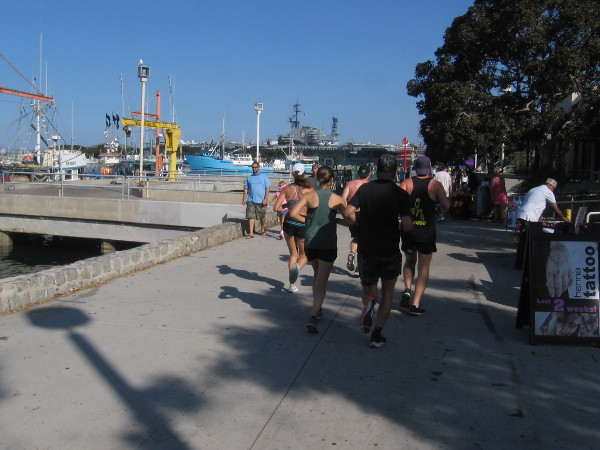 People walk and jog along San Diego's Embarcadero near Tuna Harbor.