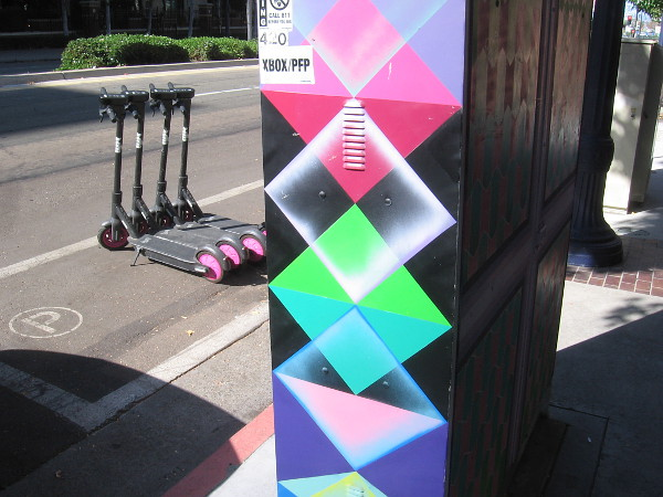Geometric street art near scooters parked in a neat line.