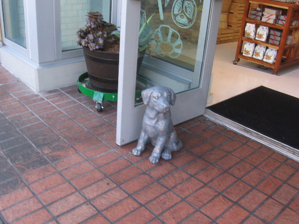 Sculpted dog holds open a shop door.