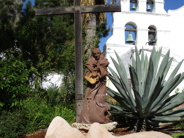 Sculpture of Fray Junípero Serra in front of the Mission San Diego de Alcalá facade.