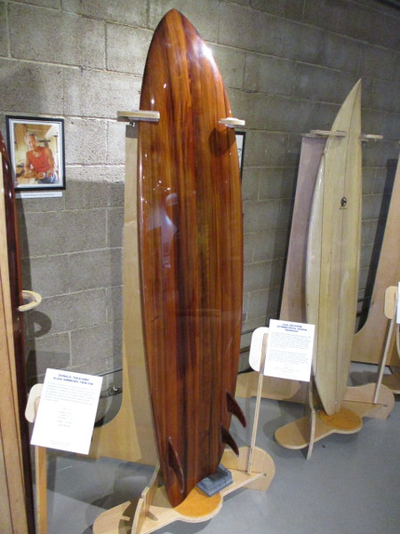 Asymmetrical redwood surfboard made from the wood of a large wine barrel, created by Carl Ekstrom.
