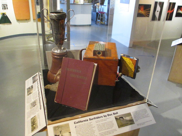 Display case holds 1946 California Surfriders book by Doc Ball, his wood waterbox camera for surf photography, and the 1928 Tom Blake Perpetual Trophy.