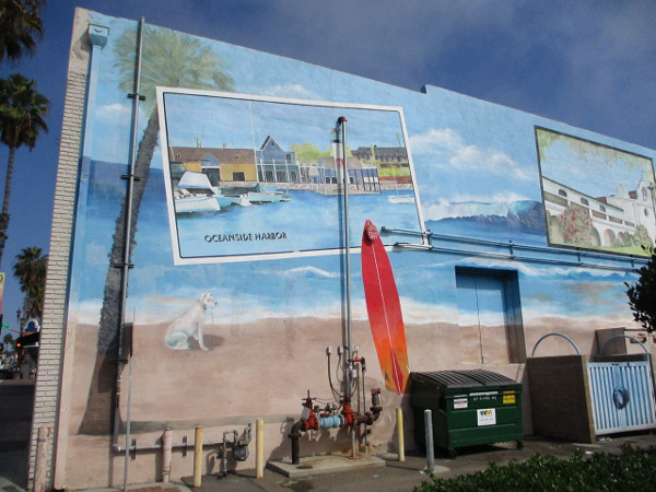 Large mural behind building at Pier View Way and North Coast Highway depicts Oceanside attractions as postcards.