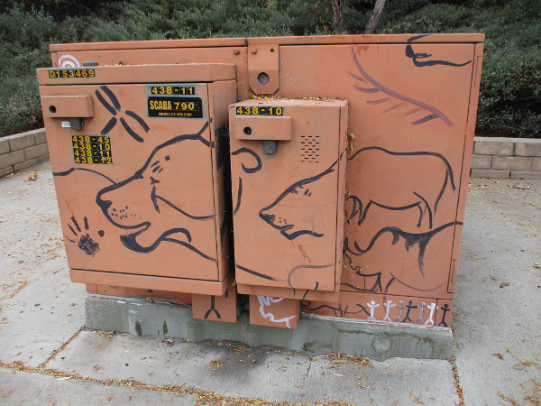 Electrical box painted with art that seems prehistoric.